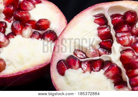 A pomegranate cut in two on a black background