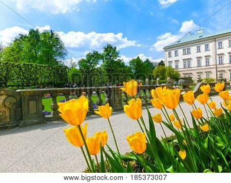 The people going at the beautiful Mirabell gardens in Salzburg. It is a popular destination visited by tourists at Salzburg, Austria