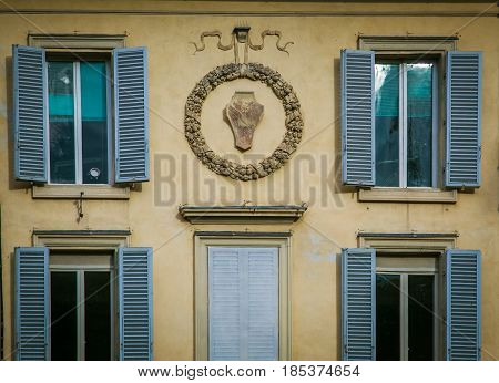 Symbol on a wall with window and shutters