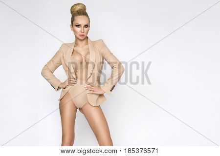 Elegant Female Model In A Suit Jacket And Nude Slimming Lingerie Standing On A White Background And