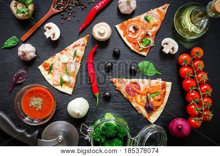 Italian pizza with ingredients and vegetables on dark table. Flat lay, top view. Sliced pizza pattern
