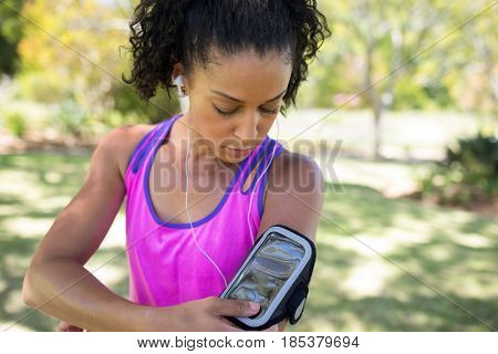 Close-up jogger woman touching the mp3 player in armband