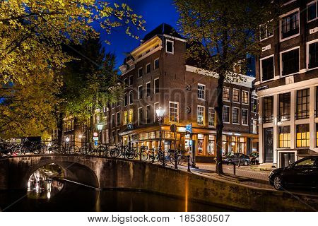 Night shot of Amsterdam canal city view with bicycles on the bridge, Netherlands