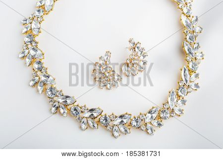 Diamonds Necklace A White Background. Stylish Necklace With Colorful Stones. A Round Gold Metal Neck