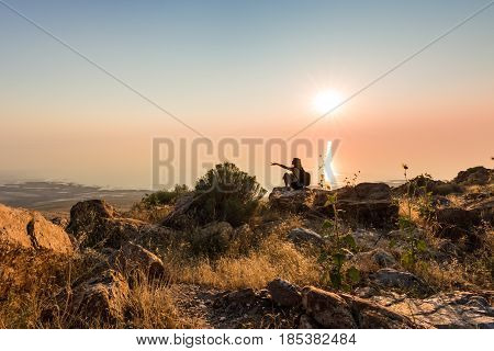 Sunset at the top of Antelope Island with silhouette of female pointing near Salt Lake City Utah.