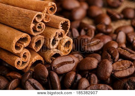 Coffee Beans And Cinnamon On A Background Of Burlap. Roasted Coffee Beans Background Close Up. Coffe