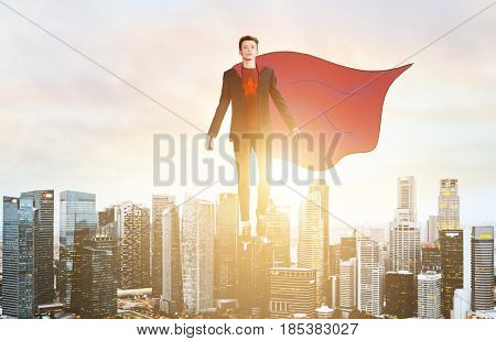 Business superhero. Businessman hovering over down town on sunset.