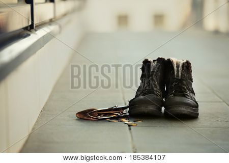 Dirty boots and wallet on the street