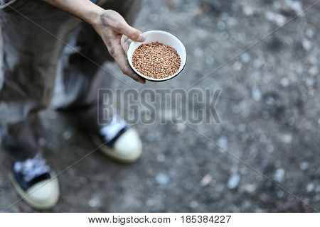 Poor man holding bowl with buckwheat