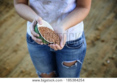 Poor woman holding bowl with buckwheat