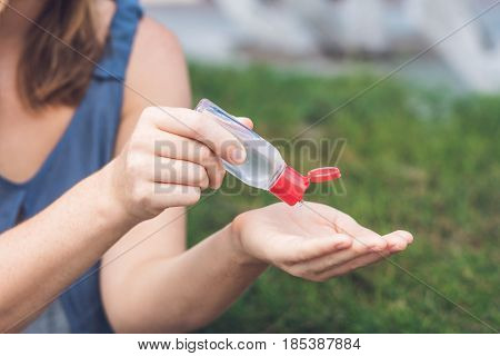 Women's Hands Using Wash Hand Sanitizer Gel Pump Dispenser
