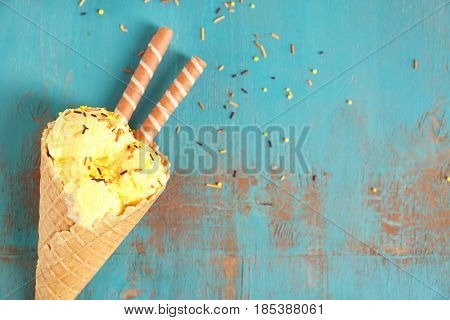 Delicious ice cream with wafer rolls in waffle cone and sprinkles on wooden background