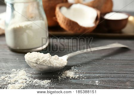 Coconut flour in metal spoon against blurred background