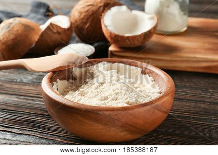 Coconut flour in bowl on dark wooden table