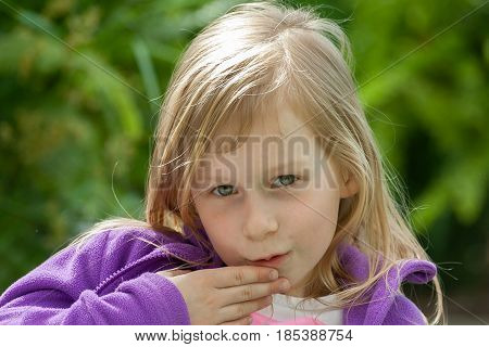 a portrait of a little girl in a lilac jacket on the background of green leaves in the garden, a hand near the mouth, a little gossip, a secret to tell sarcastically, wheat hair,portrait in front