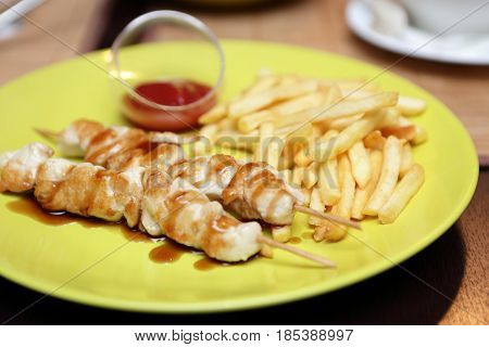 Chicken kebab with french fries on a plate