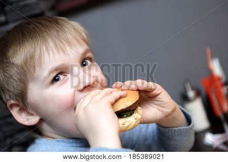 Hungry child biting burger in a restaurant
