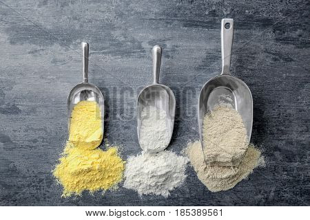 Scoops with different types of flour on wooden background