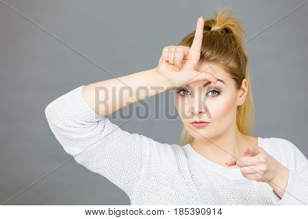 Woman Showing Loser Gesture With L On Forehead