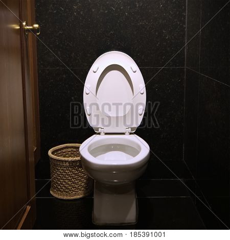 A white flush toilet in a hotel bathroom.