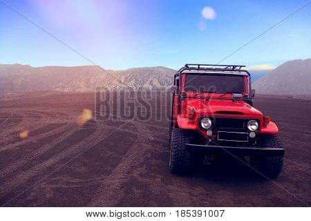 A red off-road vehicle in open space.