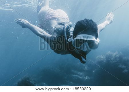 Young woman free diver swimming underwater with mask and snorkel among seaweed.