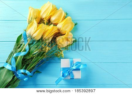 Bouquet of beautiful flowers and giftbox on wooden background