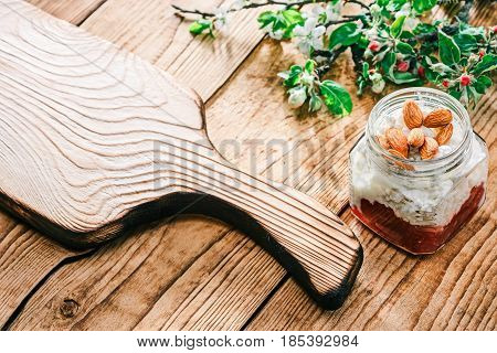 Homemade ricotta with red marmalade and almond nuts in glass jar. Raw wood background with apple and plum blooming twigs. Frame of rustic serving board. Selective focus