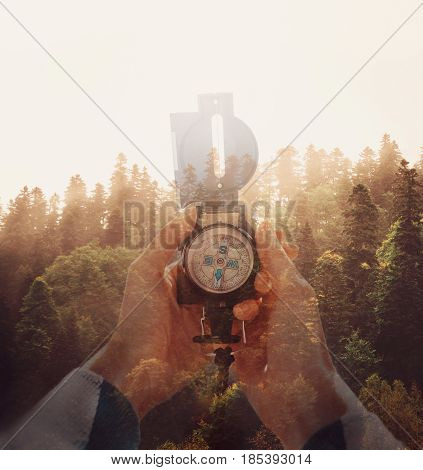 Double exposure image sunset in pine tree forest and female hands with hiking compass.