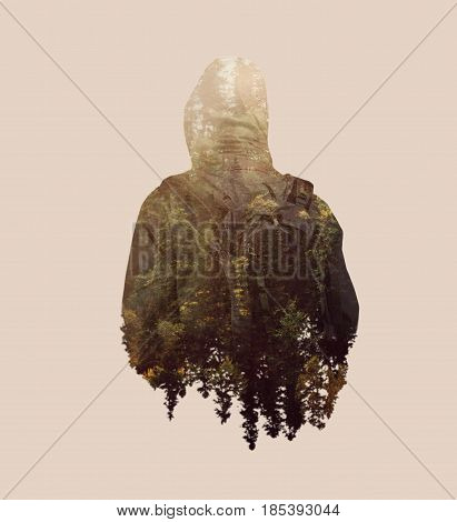 Double exposure image of male backpacker and pine tree forest.