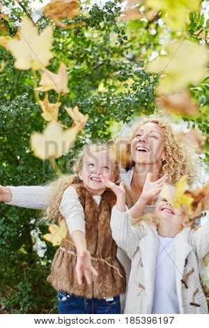 Kids playing with leaves in the park with their mother with enthusiasm