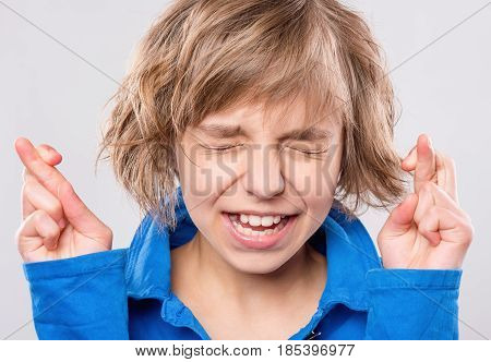 Emotional portrait of caucasian hopeful little girl crossing her fingers. Beautiful human face expression and emotions. Child praying or making luck gesture, on gray background.