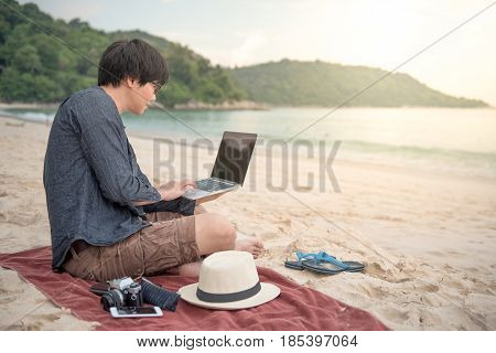 Young Asian man working with laptop computer on tropical beach digital nomad lifestyle or freelance job concepts