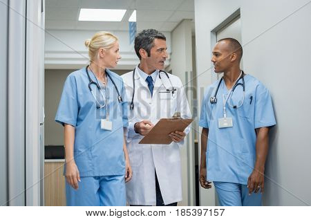 Mature doctor discussing with nurses in a hallway hospital. Doctor discussing patient case status with his medical staff after operation. Doctor holding clipboard while in conversation with nurse.