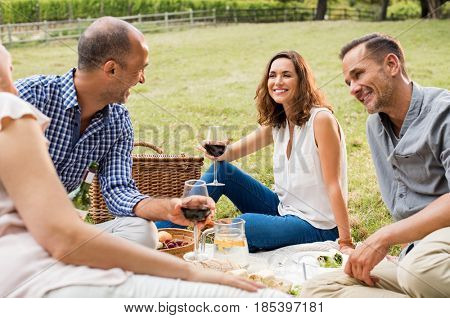 Group of mature friends enjoying a picnic sitting at park. Senior couples having lunch together and drinking red wine. Smiling women and happy men talking to each other in a conversation outdoor.