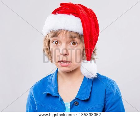 Attractive confused little girl wearing Santa Claus hat. Funny cute child 10 year old worried and scared making face with mouth open in amazement on gray background. Winter holiday christmas concept.