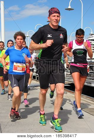 Genoa Italy - May 07 2017: Stragenova second run 10-kilometer race for city streets - athletes during the passage in the ancient port of Genoa, with ships in the background, after 8 kilometers of race
