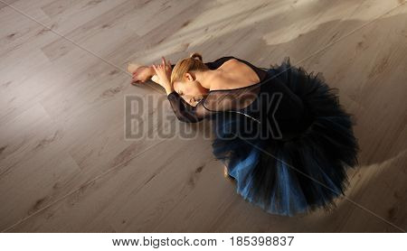 Top View Of Professional Ballerina In Blue Tutu And Pointe Shoes Sit And Stretching On Floor. Copysp