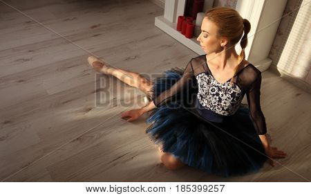 Ballet Dancer Sitting On The Wooden Floor. Female Ballerina Having A Rest. Ballet Concept.