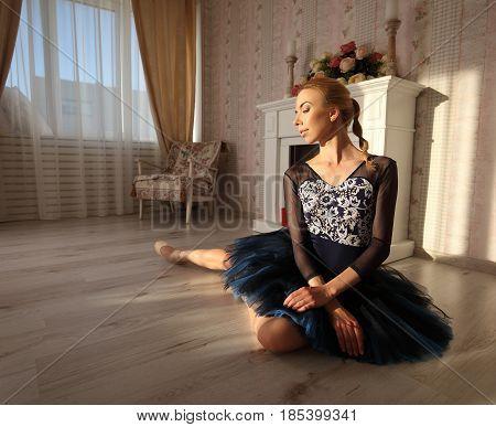 Portrait Of A Professional Ballet Dancer Sitting On The Wooden Floor.