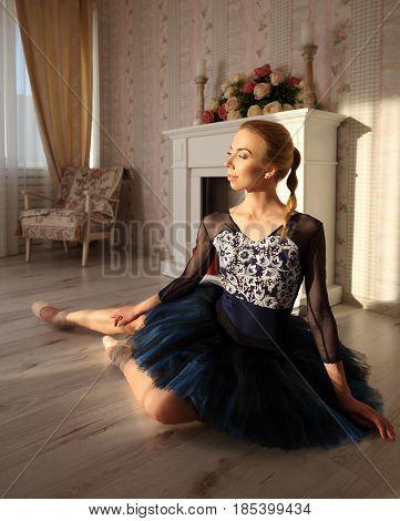 Portrait Of A Professional Ballet Dancer Sitting On The Wooden Floor. Ballet Concept.