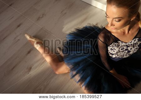 Top View Of Professional Ballerina In Blue Tutu And Pointe Shoes Sit On Floor. Copyspace