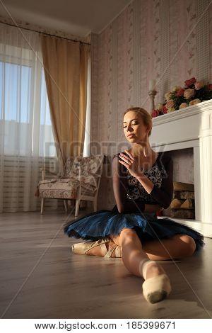 Portrait Of A Professional Ballet Dancer Sitting On The Wooden Floor. Female Ballerina Having A Rest