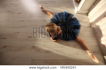 Beautiful Young Woman Ballerina Stretching Warming Up In Home Interior, Split On Wooden Floor