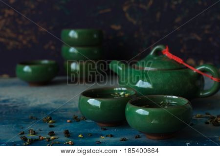 Traditional green Chinese teapot and cups against a dark background