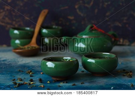 Green Chinese teapot and two cups against a dark background