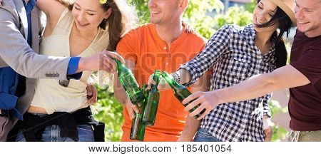 group of young friends drinking, toasting with bottles of beer and having fun outside in a park