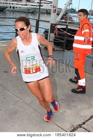 Genoa Italy - May 07 2017: Stragenova second run 10-kilometer race for city streets - athletes during the passage in the ancient port of Genoa, with ships in the background, after 8 kilometers of race.