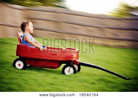 Young boy zooms downhill in wagon