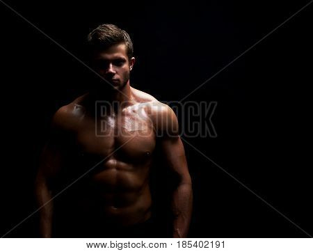 Horizontal studio shot of a young shirtless athletic man with sexy hot muscular ripped body posing on black background copyspace fitness sports athletics muscles gym physique confidence determination.